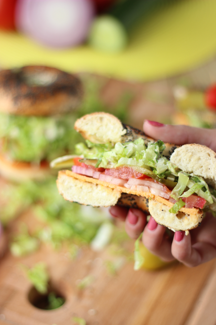 A crunchy vegan Caesar salad packed into a bagel drenched in dressing.