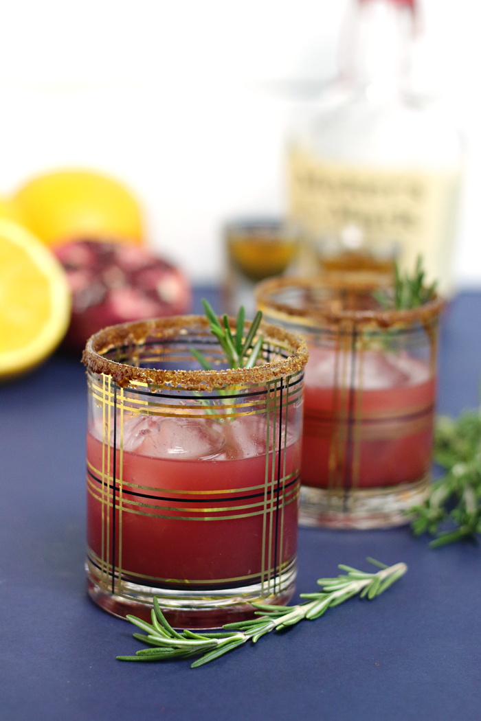 An orange and pomegranate fruity festive twist on traditional old-fashioned bourbon cocktail with a hint of rosemary.