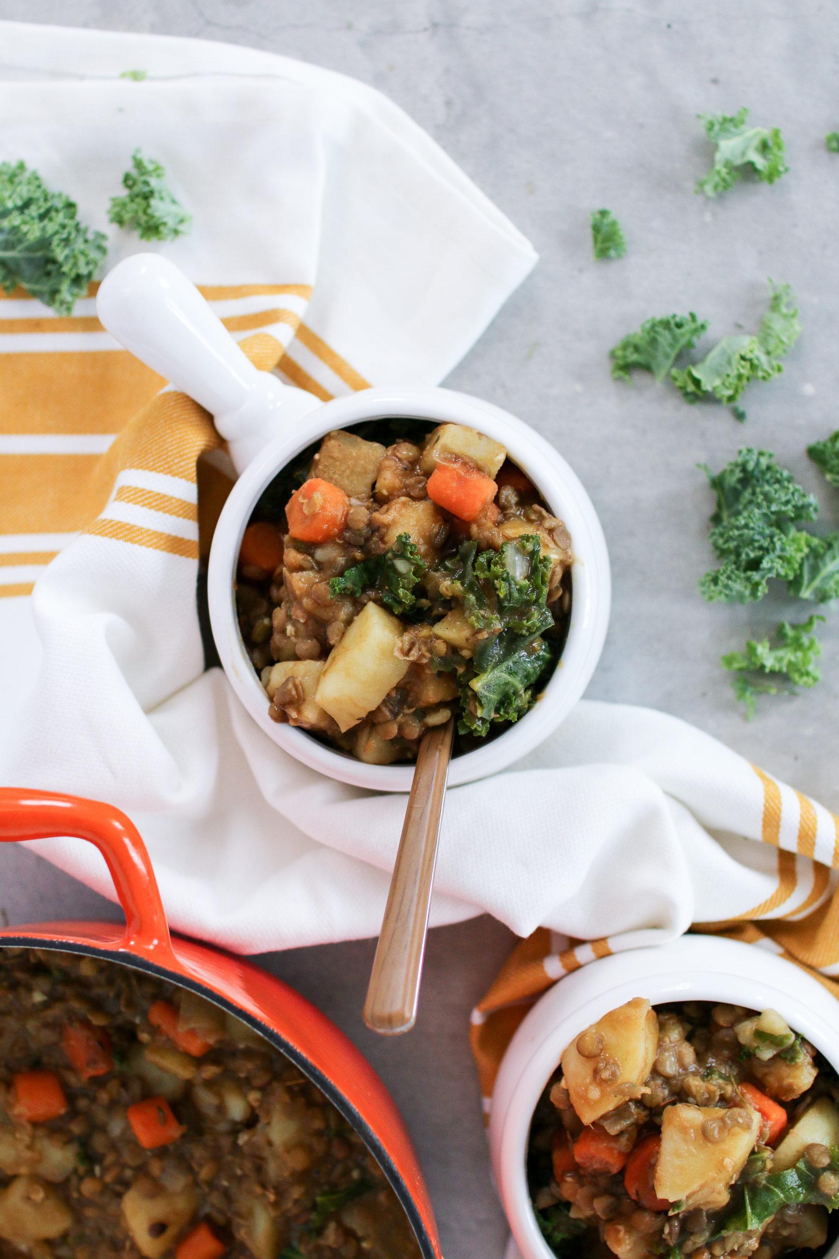 potato lentil stew in a white dish on a grey worktop