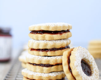 Healthier holiday linzer cookies filled with perfectly tart raspberry jam and covered in a dusting of powdered sugar for a beautiful and delicious treat!