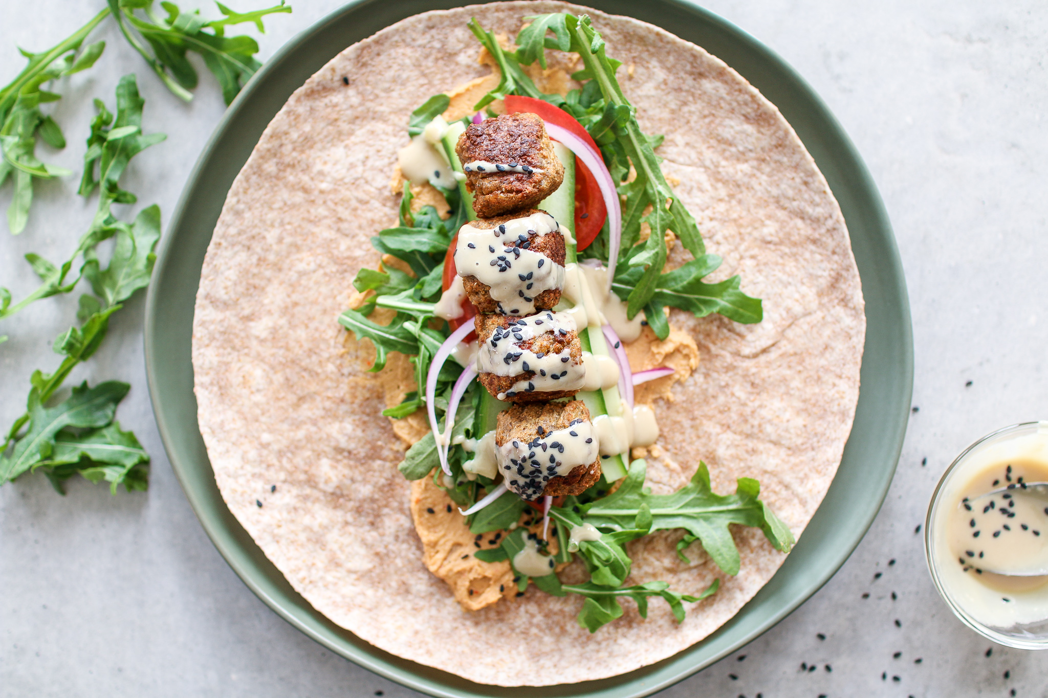 Savoury falafel, wrapped in a large tortilla smothered in red pepper hummus, topped with peppery arugula, crunchy cucumbers, tomatoes, onions and drizzled in creamy tahini.