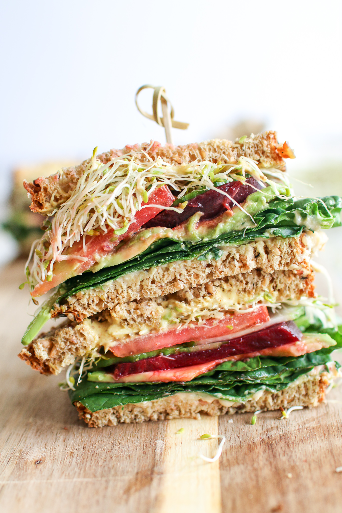 A colourful veggie sandwich stacked with fresh spinach, creamy avocado, crunchy cucumbers, tomatoes, beets and microgreens, smooshed between your favourite bread and smothered in caramelized onion hummus and creamy aioli. The ultimate sammy!