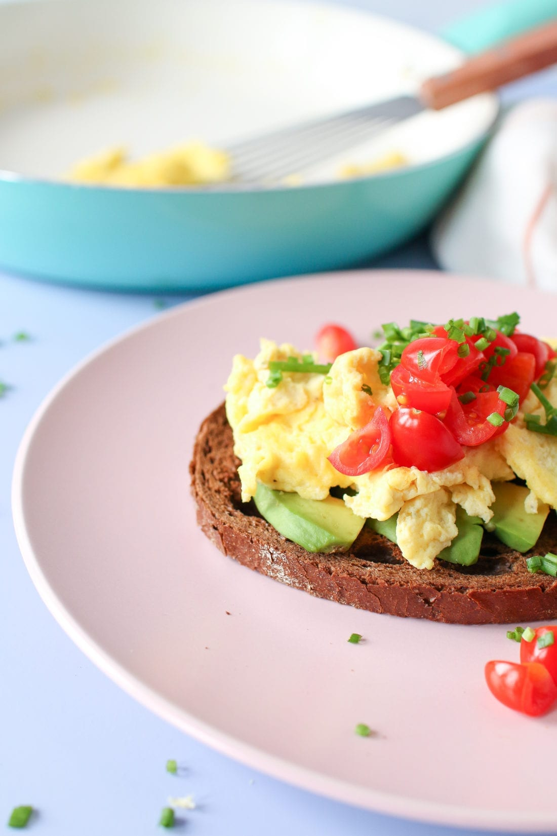 Perfectly scrambled fluffy eggs made with 2 simple ingredients- eggs and yogurt! Served on avocado toast and topped with tomatoes and fresh chives; a quick meal for breakfast or lunch.
