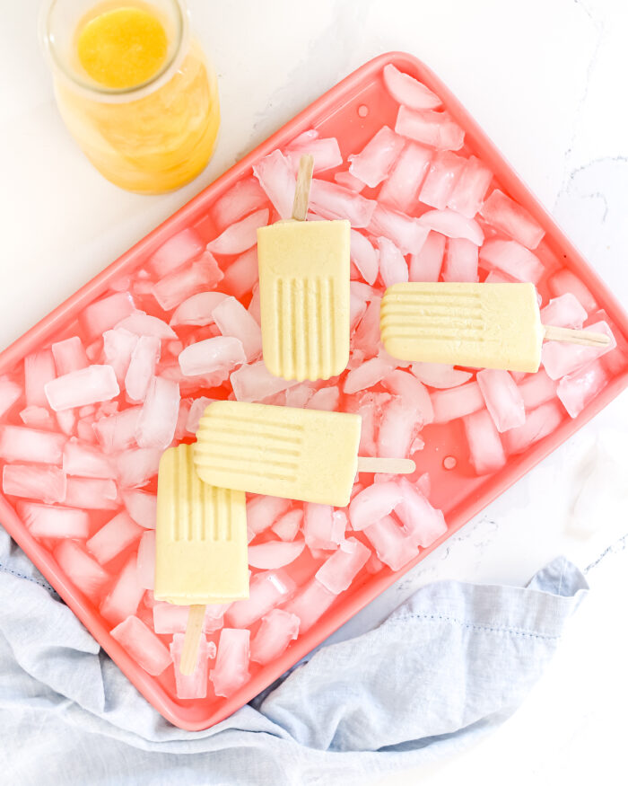 Sweet and Creamy Orange Creamsicles that are healthy, refreshing and made with simple ingredients like orange juice, coconut milk, maple syrup, greek yogurt, turmeric and vanilla extract. Reminiscent of childhood and the perfect summer treat!