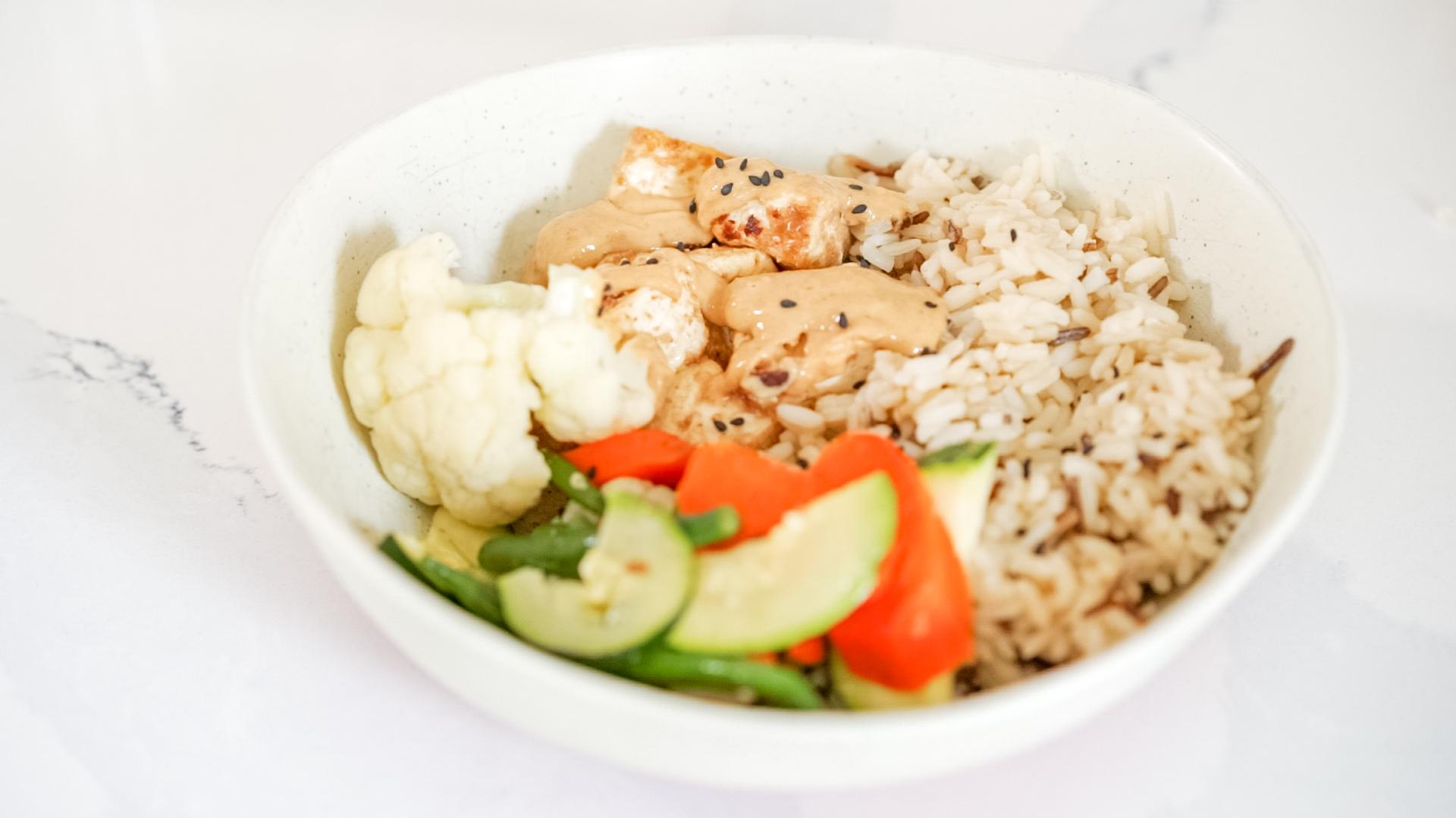 a bowl of tofu with peanut satay sauce, rice, cauliflower and salad