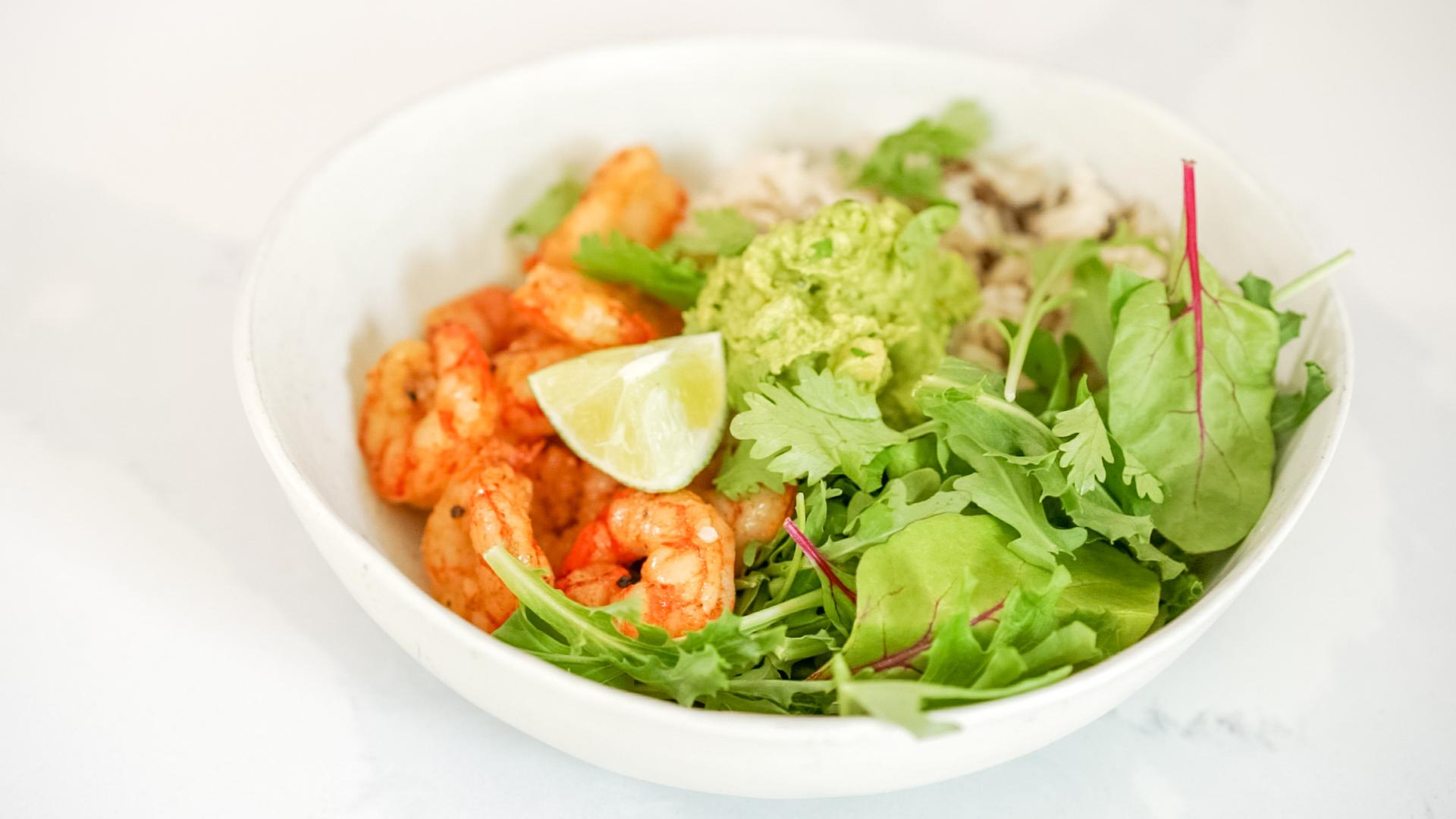 a bowl of taco spiced shrimp, rice, guacamole and salad