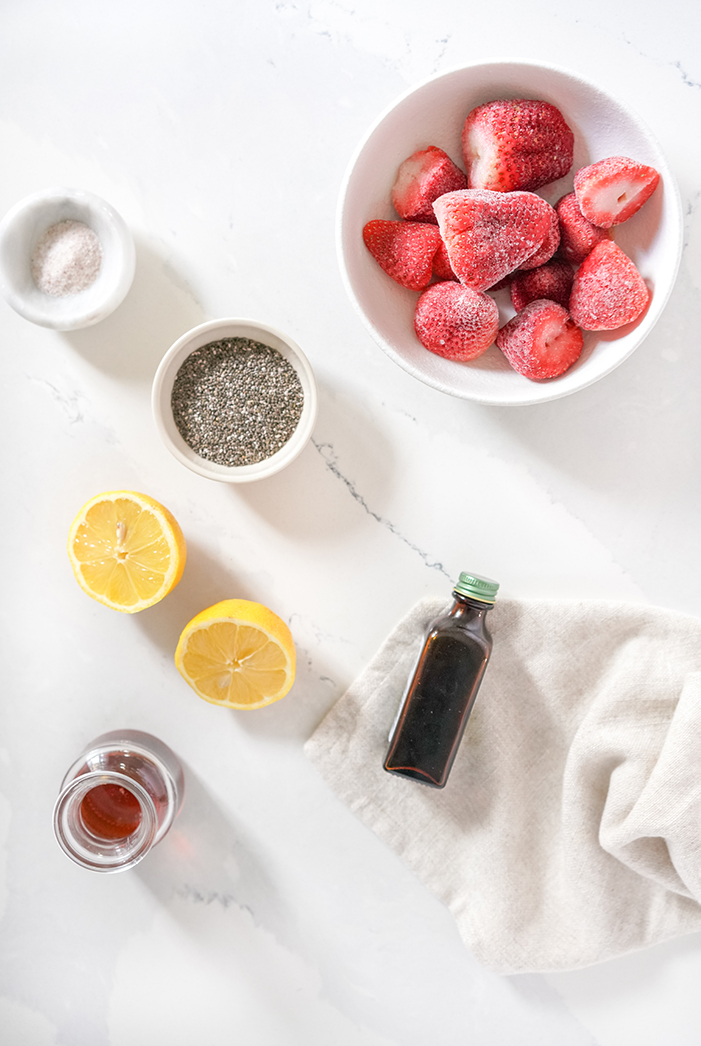 Ingredients for strawberry chia jam laid out on a white table, including frozen strawberries, chia seeds, lemon, maple syrup and vanilla essence