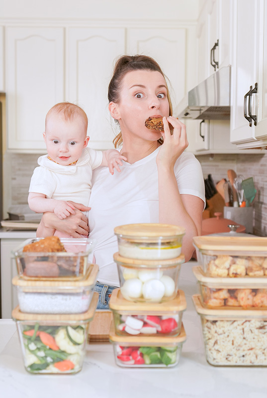 Mom holding her baby and eating meal prepped food