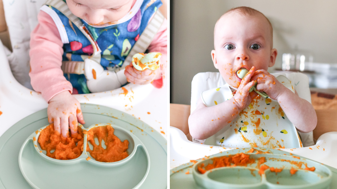 a 6 month old baby using a green plate and baby utensils to eat pureed sweet potato