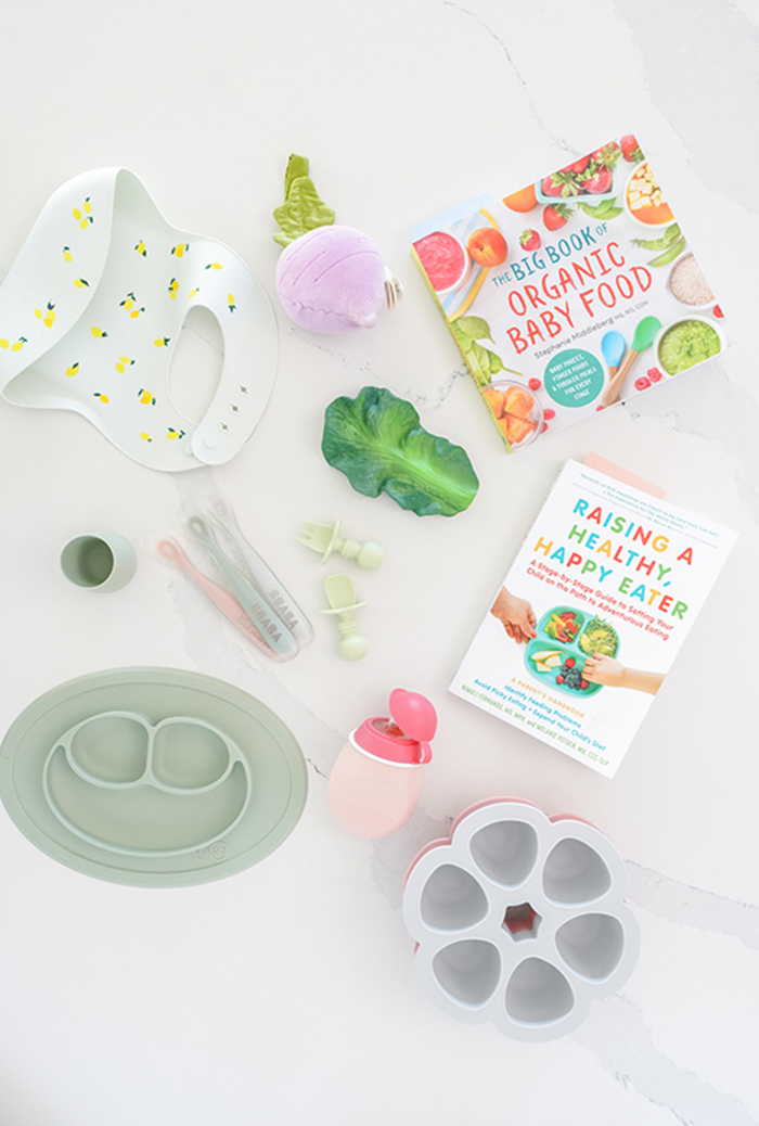a flat lay of baby food resources including baby utensils and baby cook books