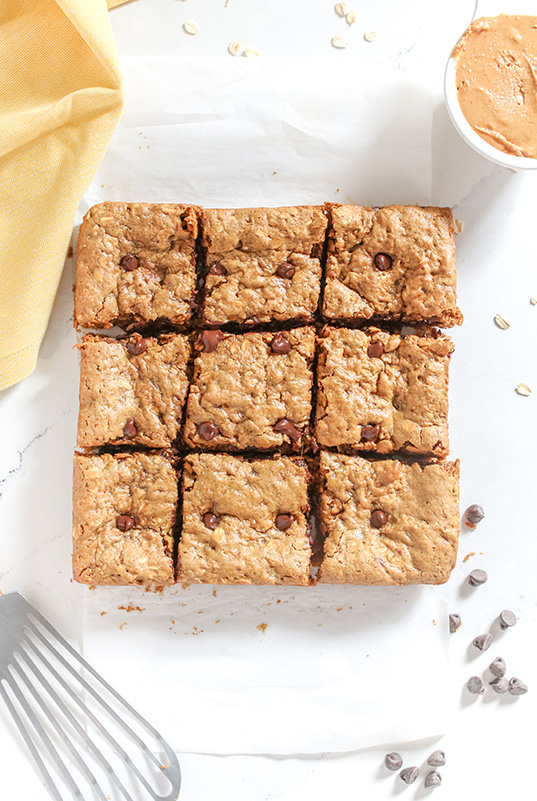 homemade peanut butter cookie bars cut up on a white surface