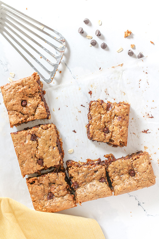 peanut butter cookie bars being served up on a white surface with a metal spatula