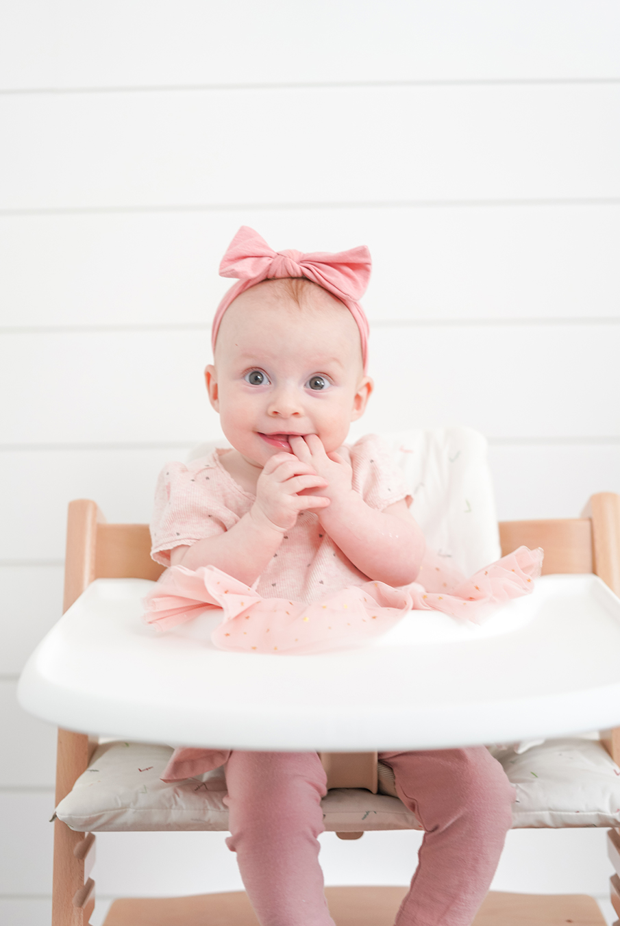 baby girl sitting in a highchair wearing pink
