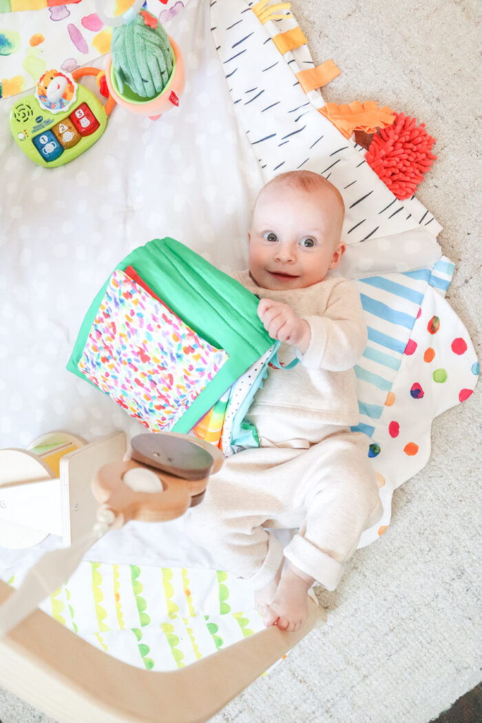 a 6 month old baby laying on a playmat with toys