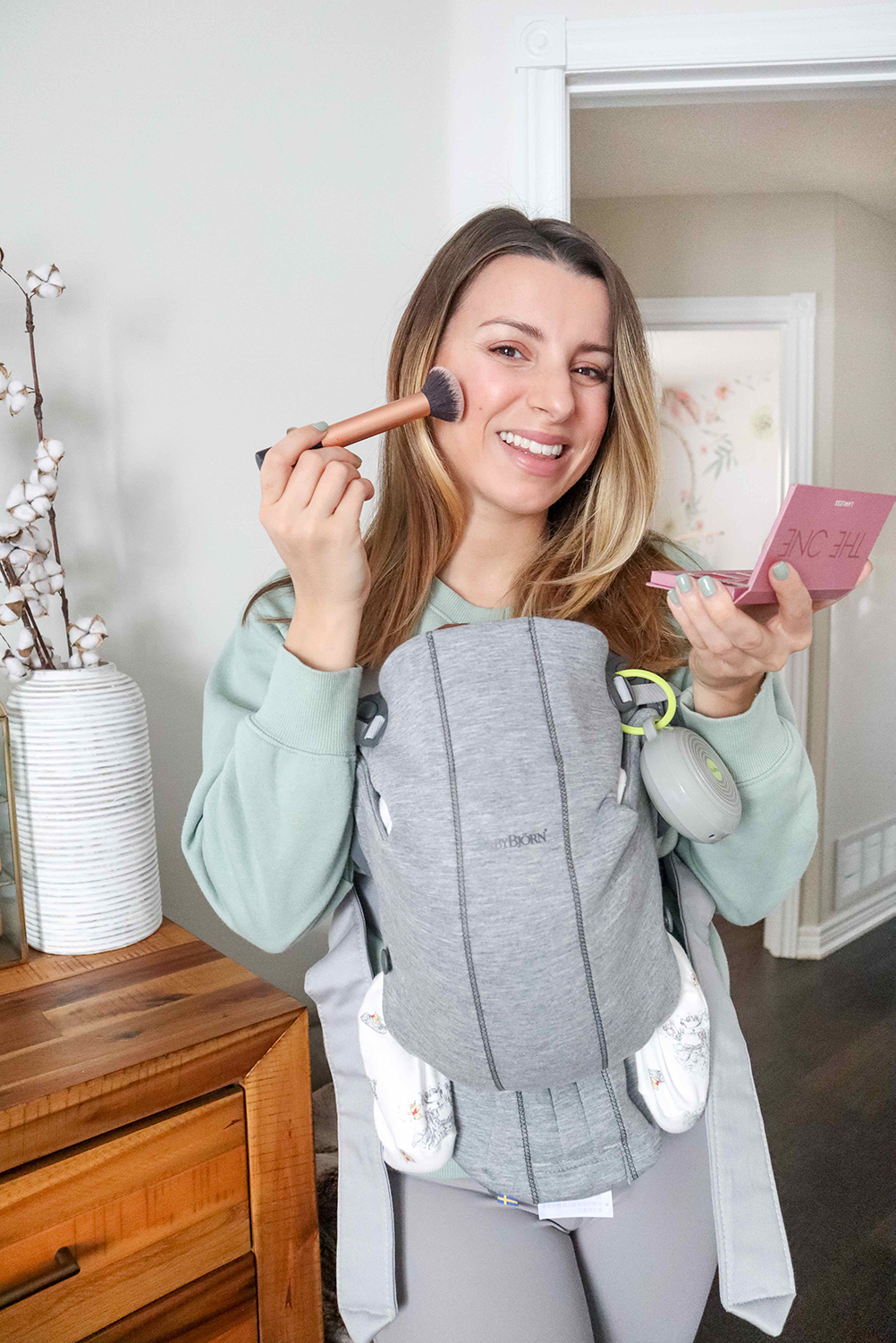 woman wearing her baby and applying natural makeup