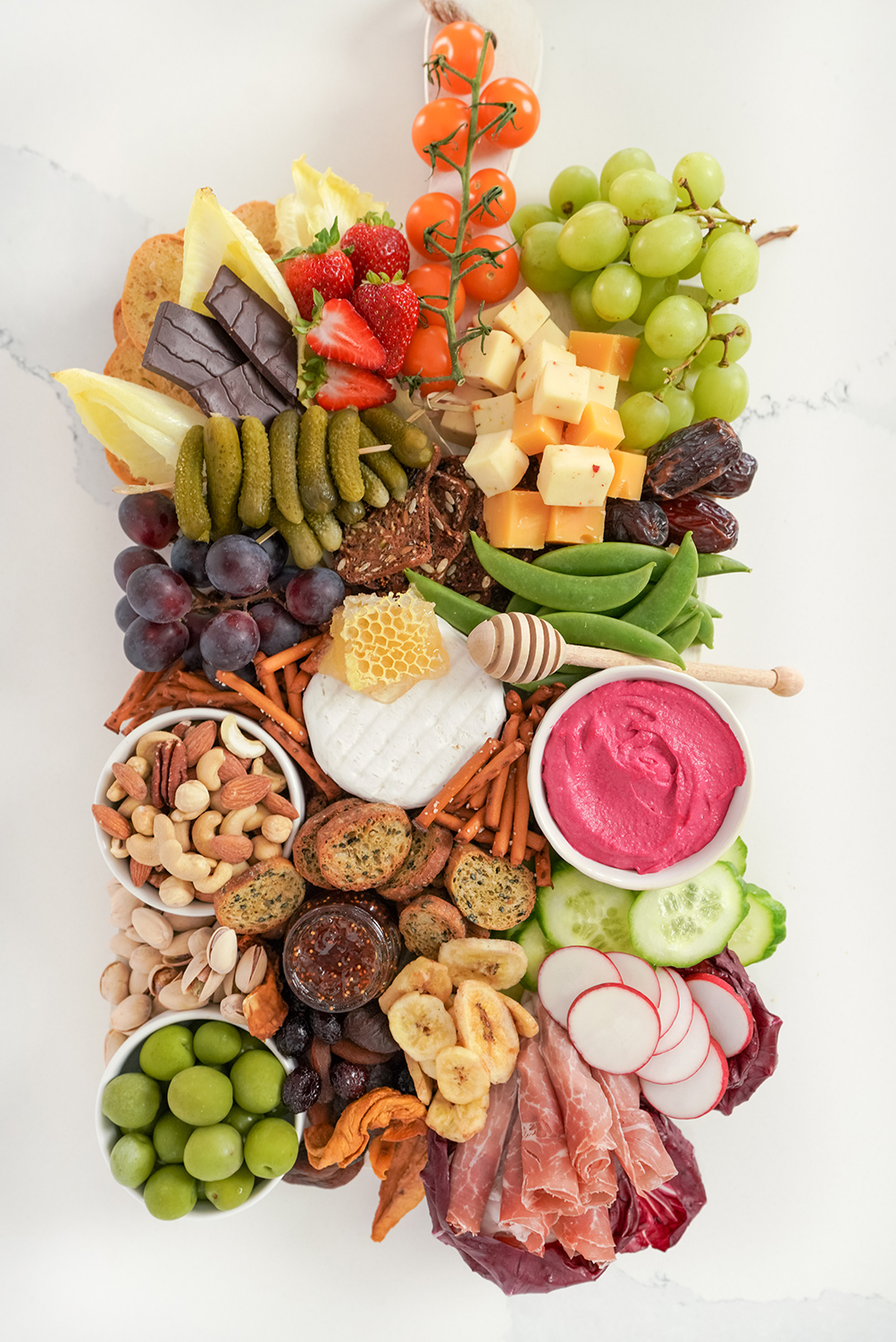 a grazing board containing fruits, veggies, cheese, crackers and cured meat