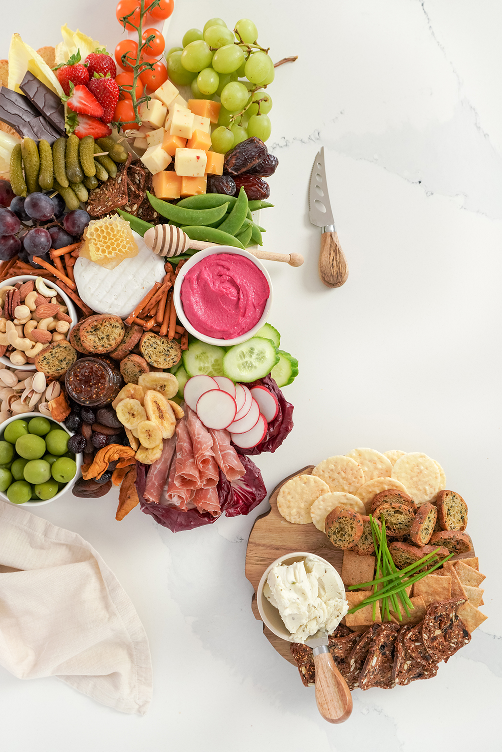 cheese, veggies, fruits and crackers on a wooden board