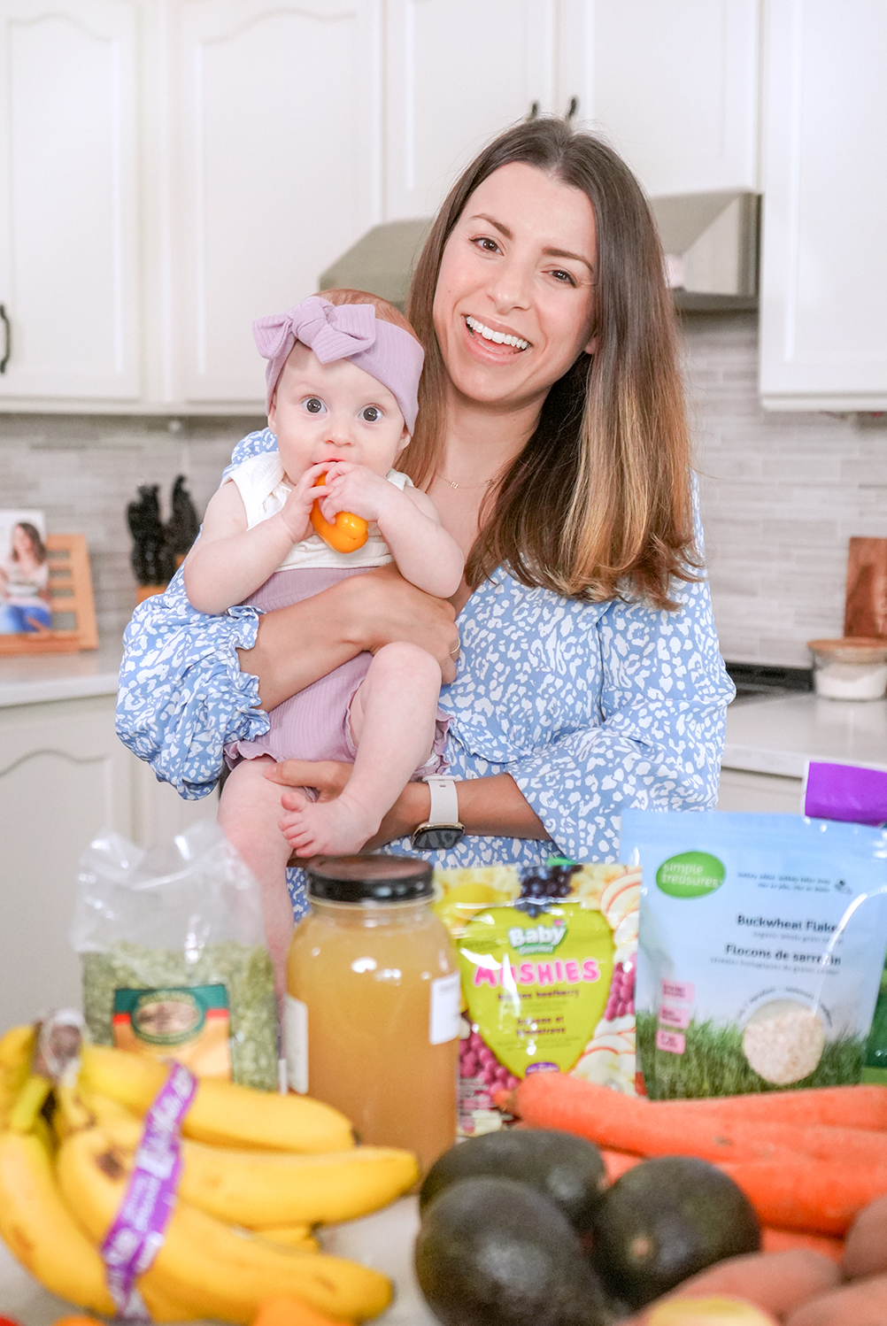Brunette woman holding her 7 month old baby and showing off baby led weaning foods in her kitchen