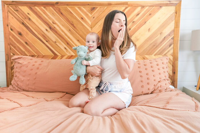 a brunette mom sitting on her bed yawning while holding her baby