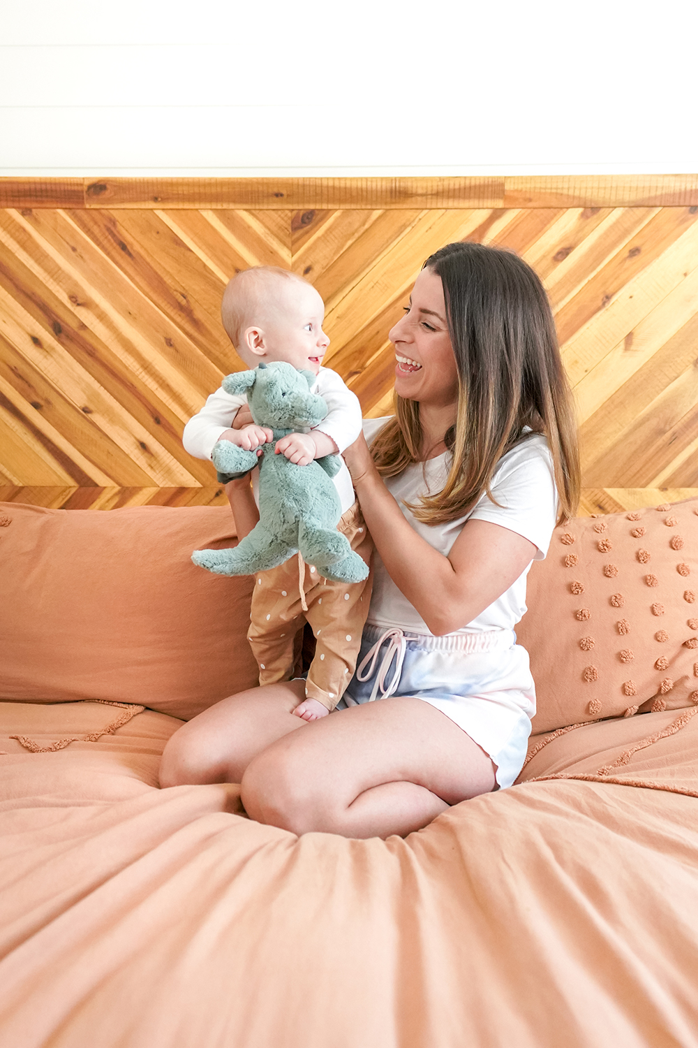 a brunette mother sitting on her bed holding her 6 month old baby