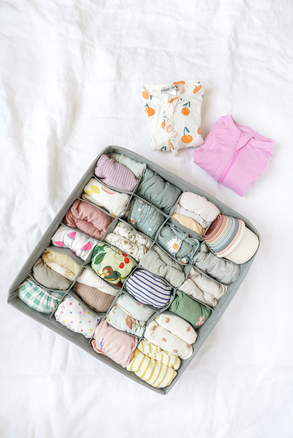 a sock organiser with baby clothes inside