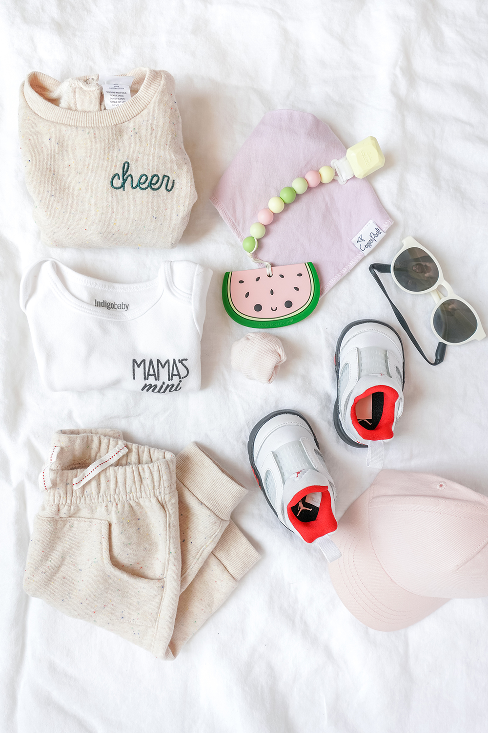 a baby outfit laid out on a white sheet
