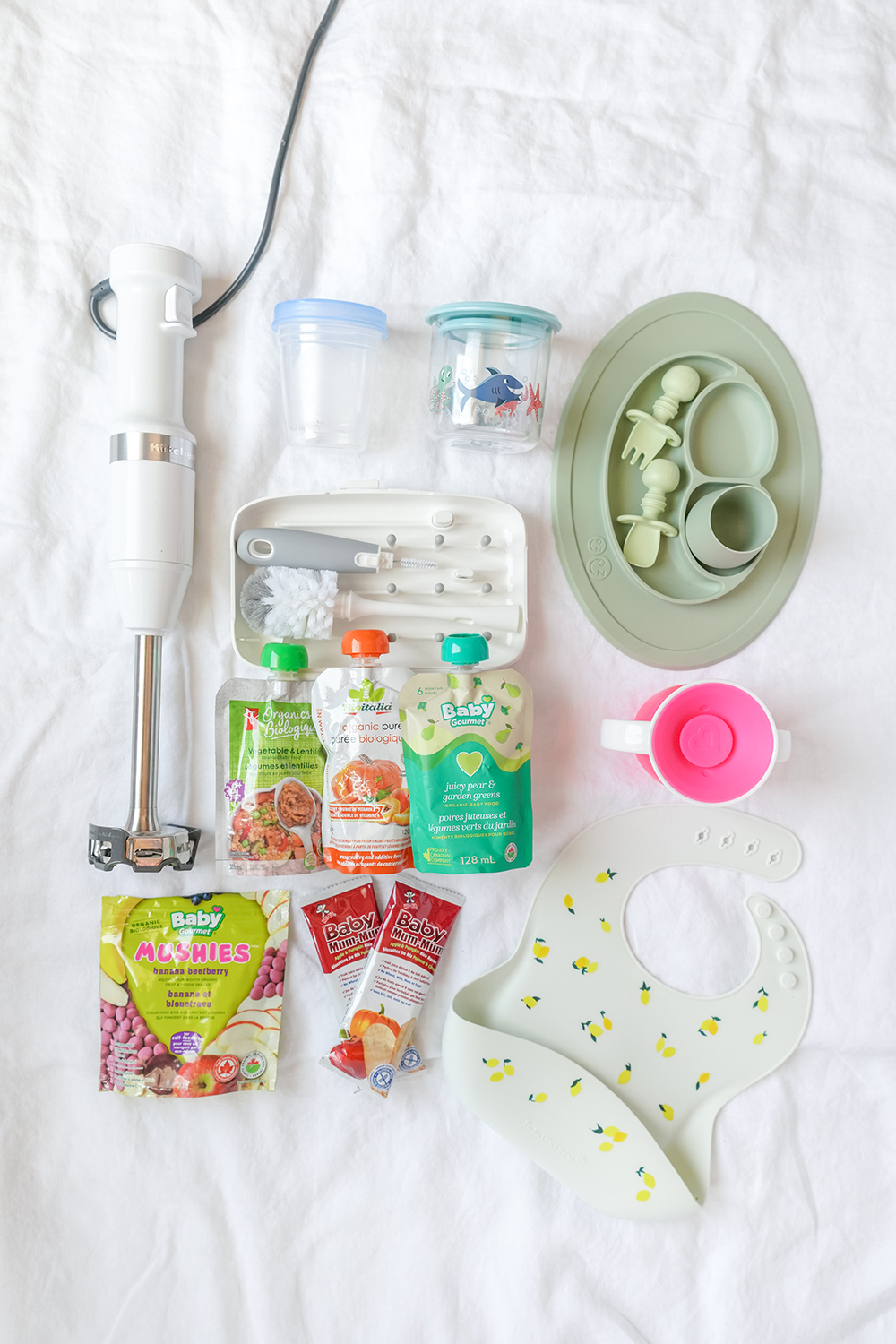a flat lay of baby food essentials on a white sheet