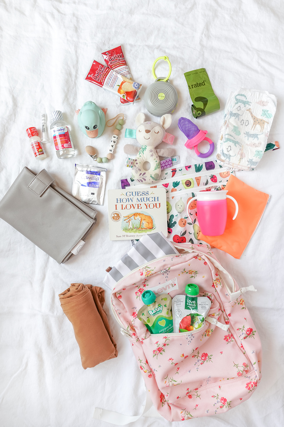 flatlay of baby travel essentials on a white sheet