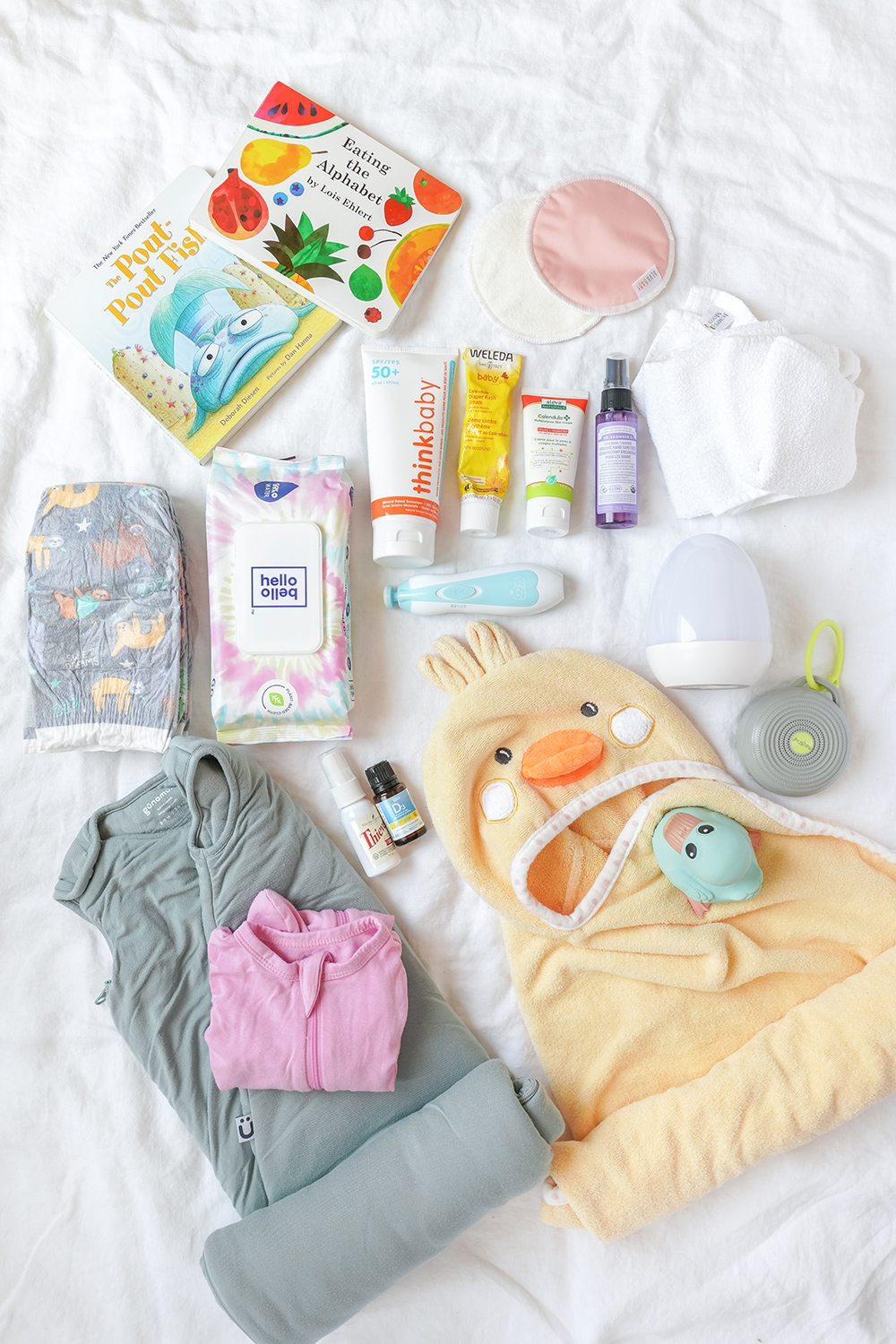 a selection of baby toiletries and sleep supplies on a white sheet