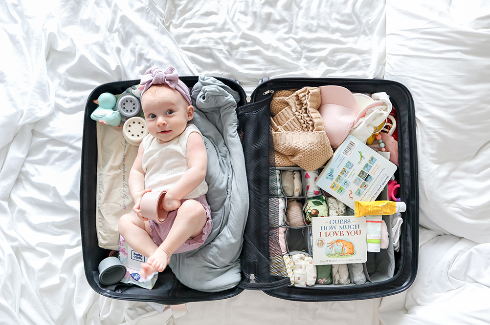 a baby in a suitcase on a white sheet
