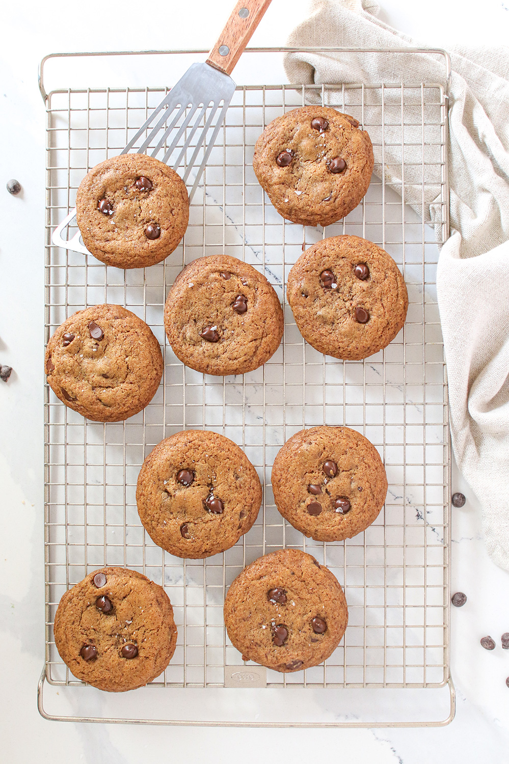 9 chocolate chip cookies on a wire cooing rack with a spatula picking one up