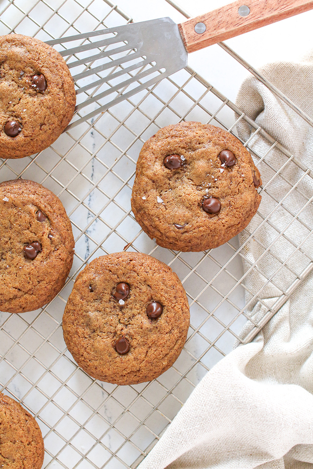a close up birds eye shot of chewy chocolate chip cookies on a wire cooling rack with a spatula picking one up