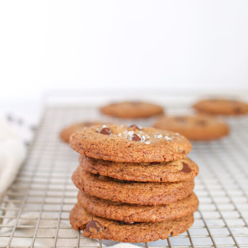 a stack of chewy chocolate chip cookies on a wire cooling rack