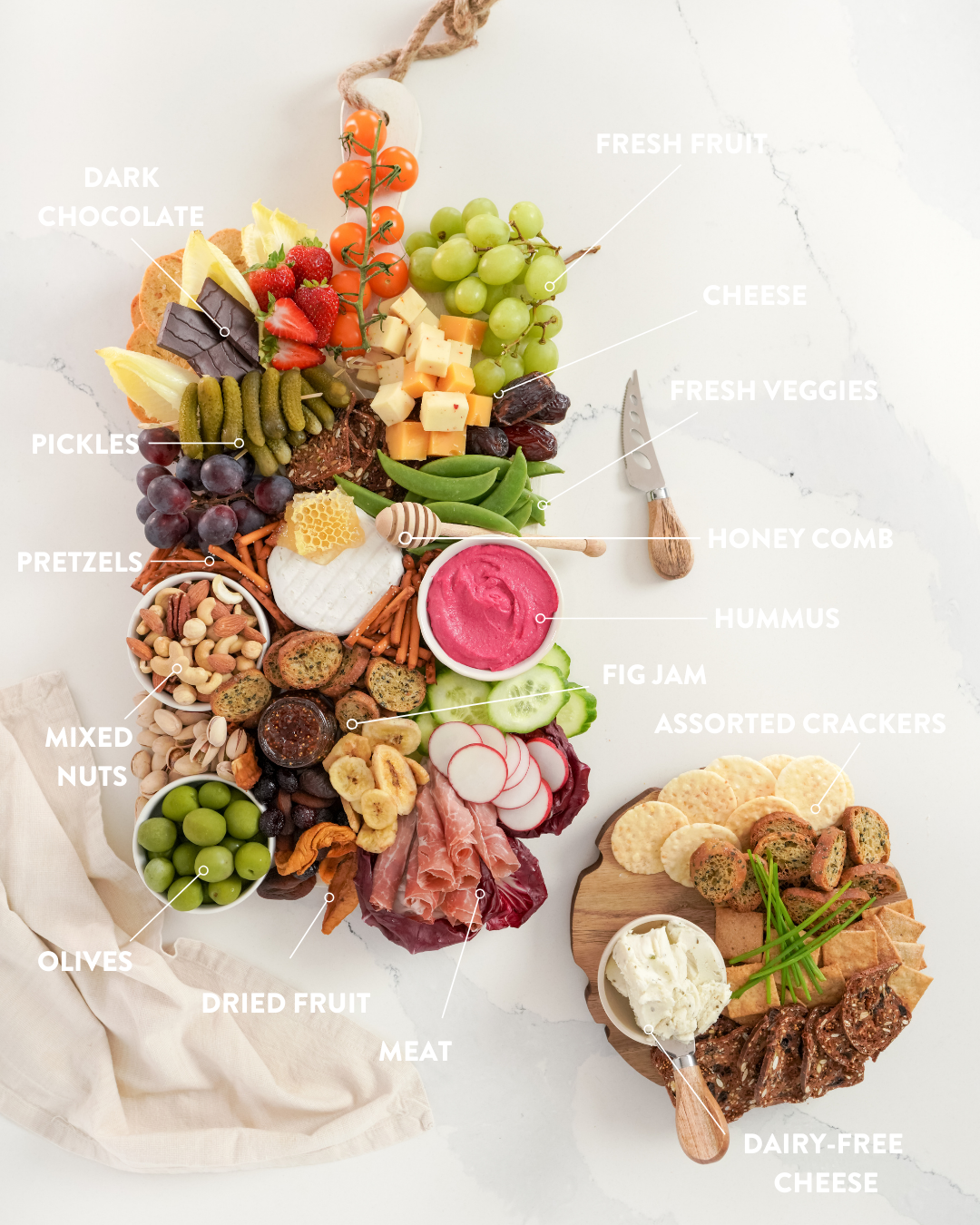 a grazing board of finger foods on a white table cloth, with white text around explaining what's on the board