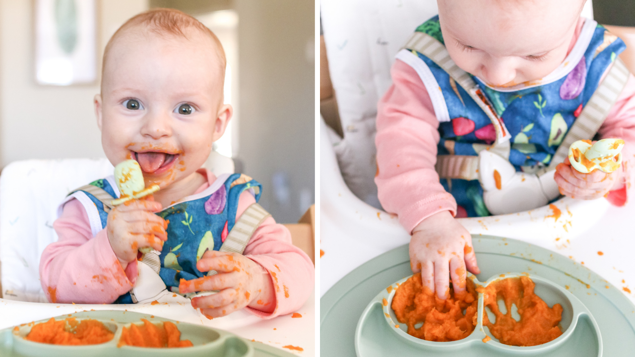 A 7 month old baby eating a carrot puree while wearing a blue bib