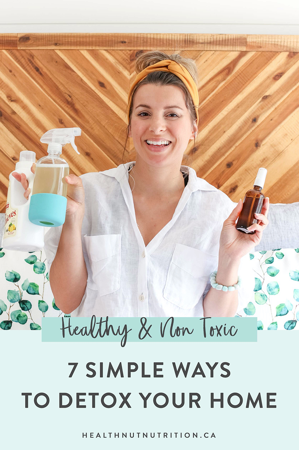 woman wearing a white shirt holding up a spray bottle and essential oils to detox your home