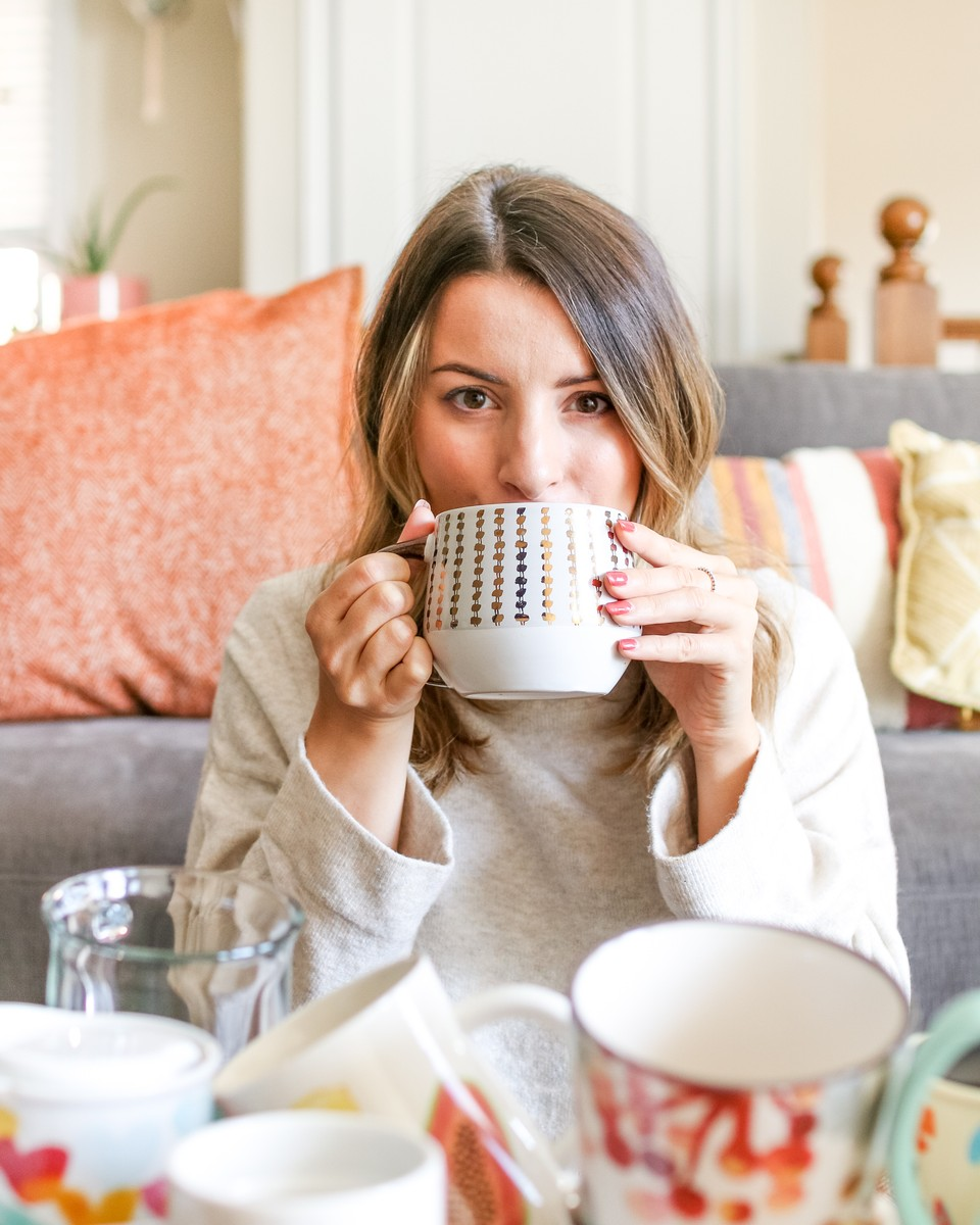 woman with brown hair drinking herbal coffee out of a black and white mug