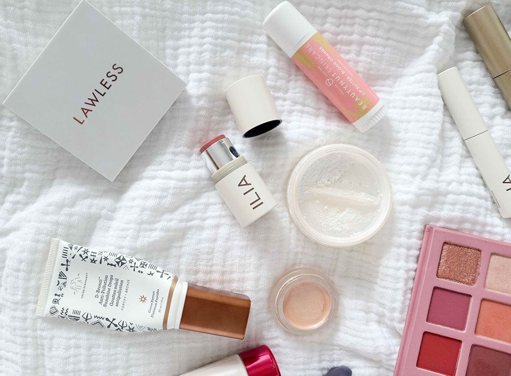 a flat lay of makeup and lip butter on a white sheet