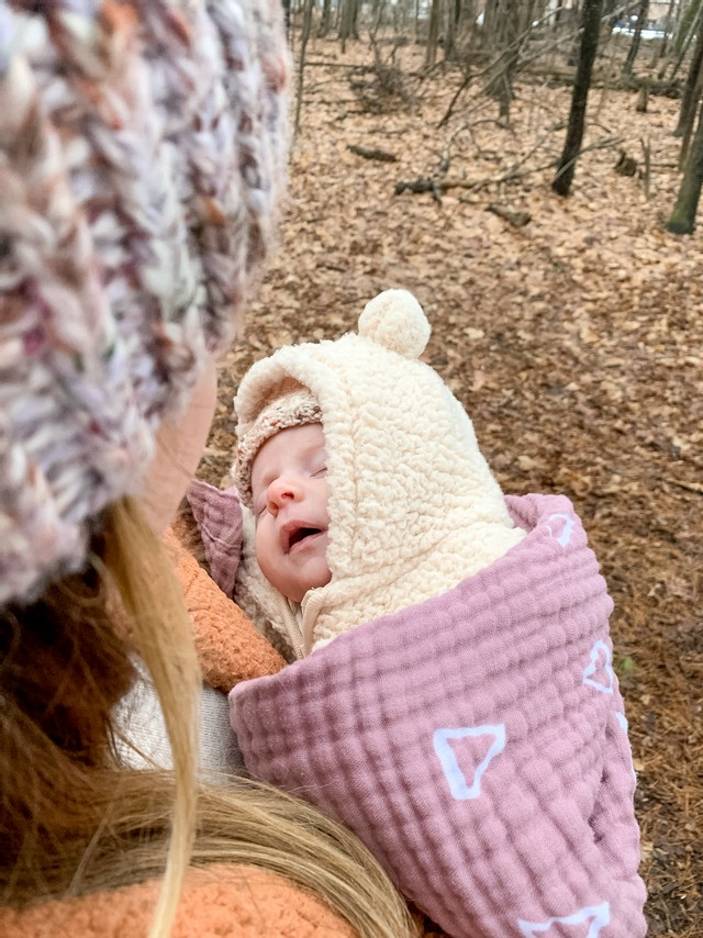 a 4-6 month old baby wrapped up in a fluffy coat and blanket, sleeping in her mother's arms