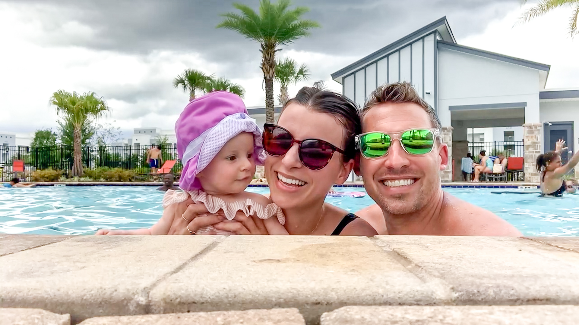 mother, father and baby in the swimming pool