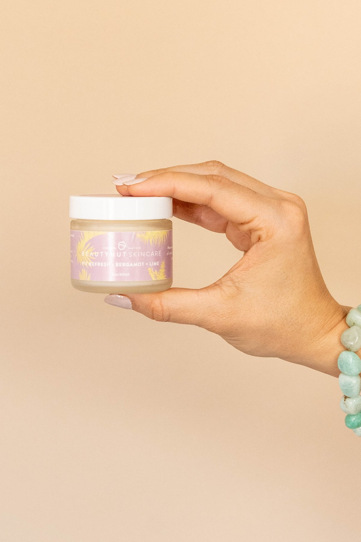 a hand holding up a pot of BeautyNut natural deodorant against a peach background
