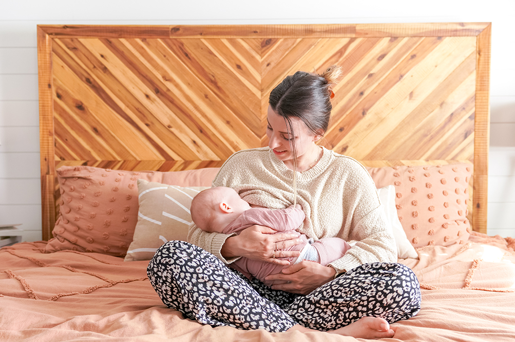 woman sitting cross legged on the bed breastfeeding her baby