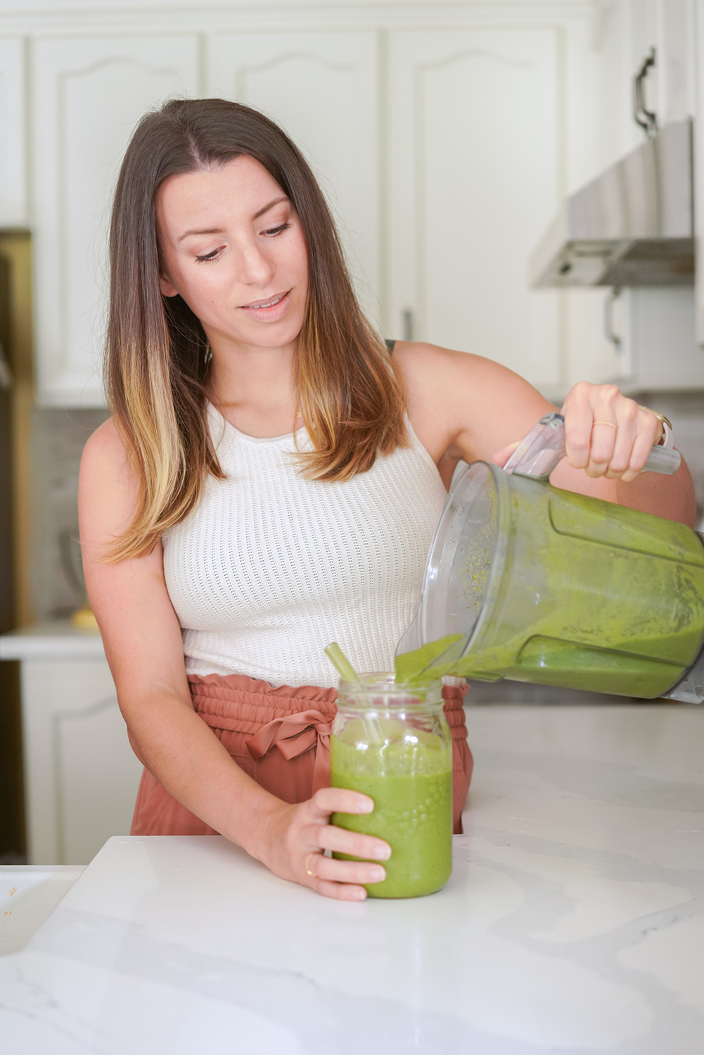 woman pouring a green smoothie into a glass