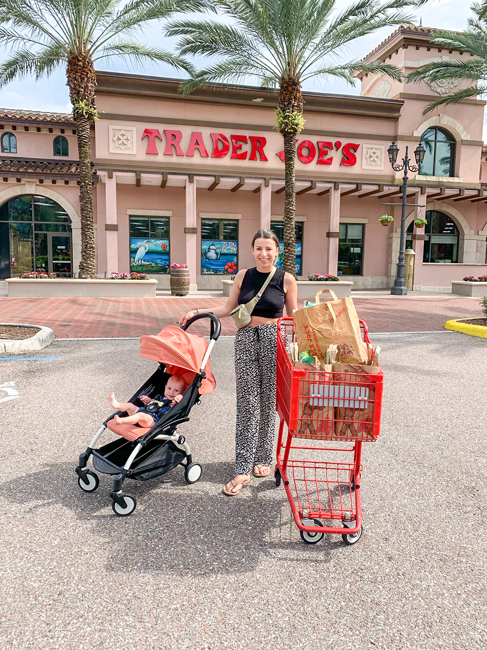 brunette woman with a baby standing outside Trader Joe's with a shopping cart