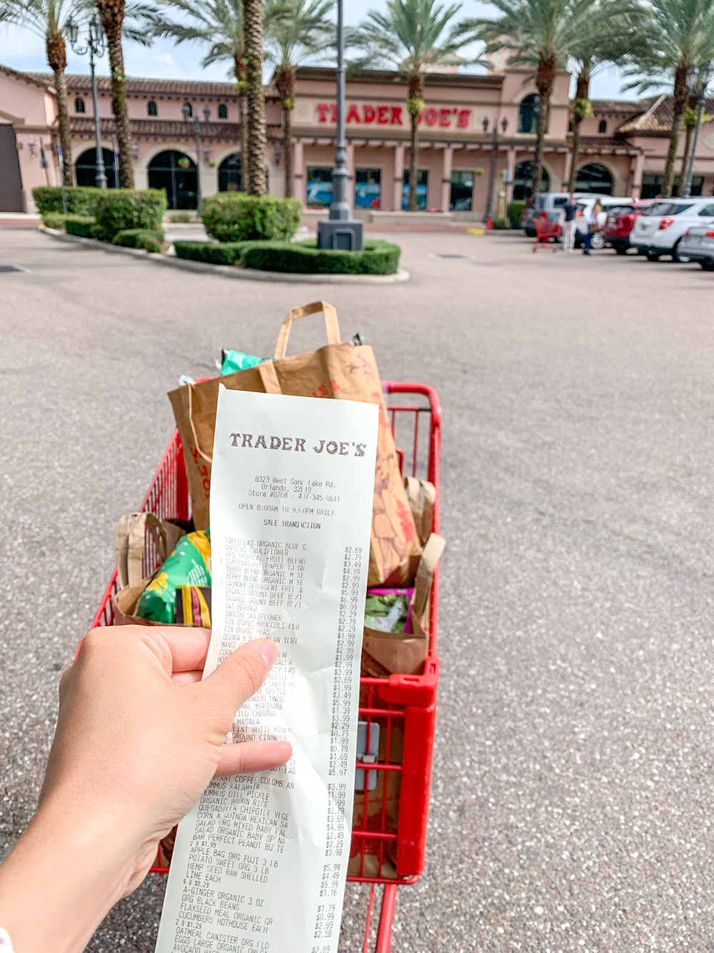a hand holding up a Trader Joe's receipt in front of a shopping cart full of food