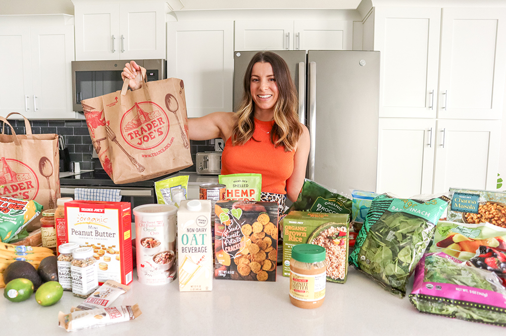 brunette woman standing in a kitchen holding up a trader joe's bag