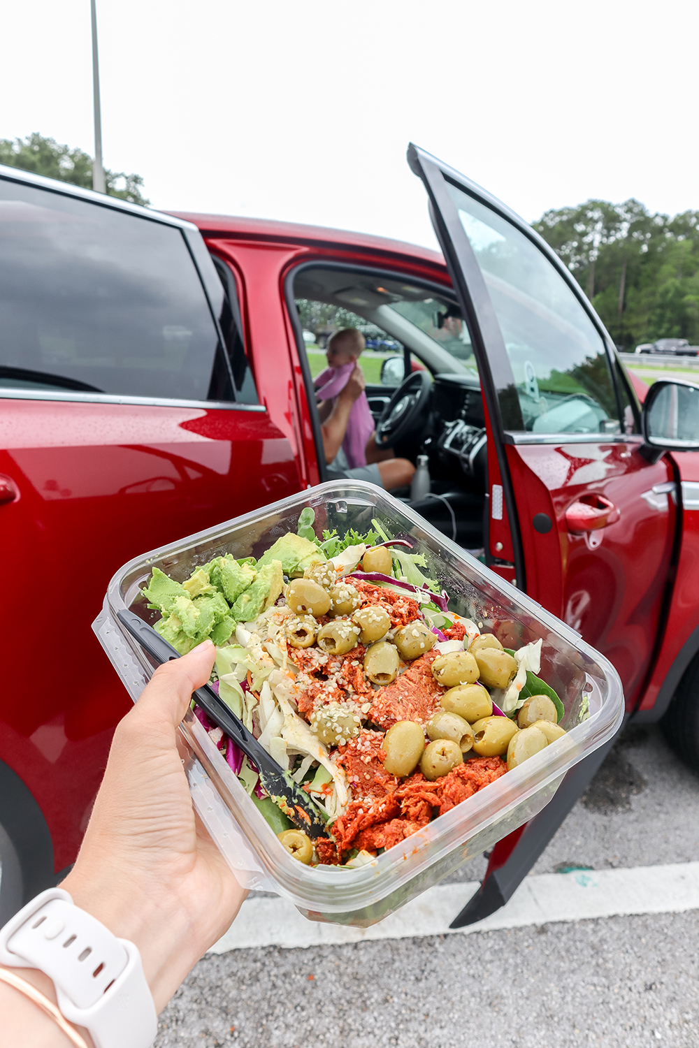 a hand holding a tuna salad in front of a car