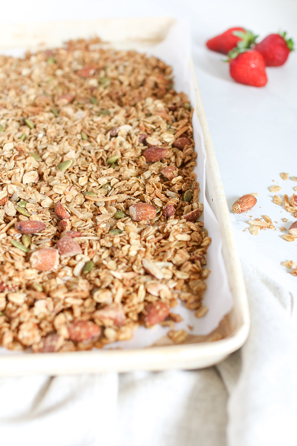 homemade granola in a white tray with strawberries next to it