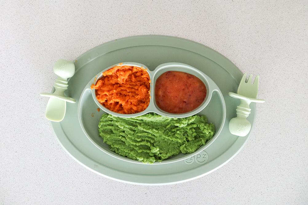 Baby food consisting of avocado, sweet potato and peaches on a green plate