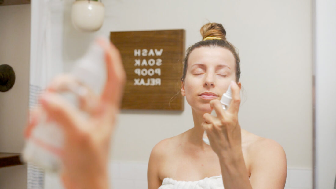 woman wearing a towel spray her face with toner